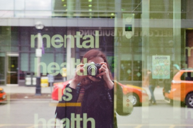 Person looking through a camera looking at her reflection in the street in a window that reads Mental health is health.