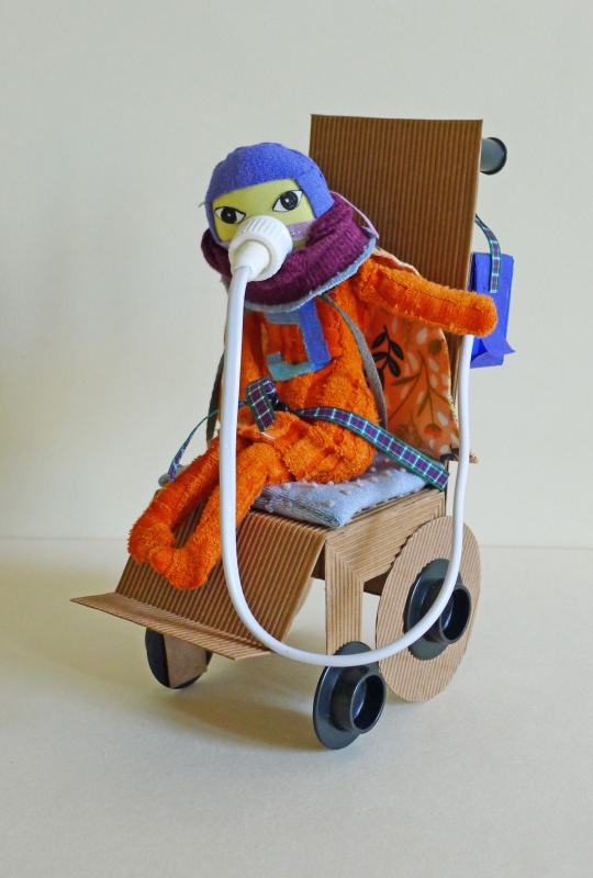 Image of an orange figure in a cardboard wheelchair, wearing an oxygen mask.
