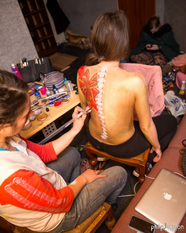 Image of the back of a topless person with long dark hair, having a spine and flowers painted on their back. The painter is wearing a red and white top, jeans and is holding a paint brush with red paint. There are painting supplies on the table next to the two people and a person in the background looking at their phone.