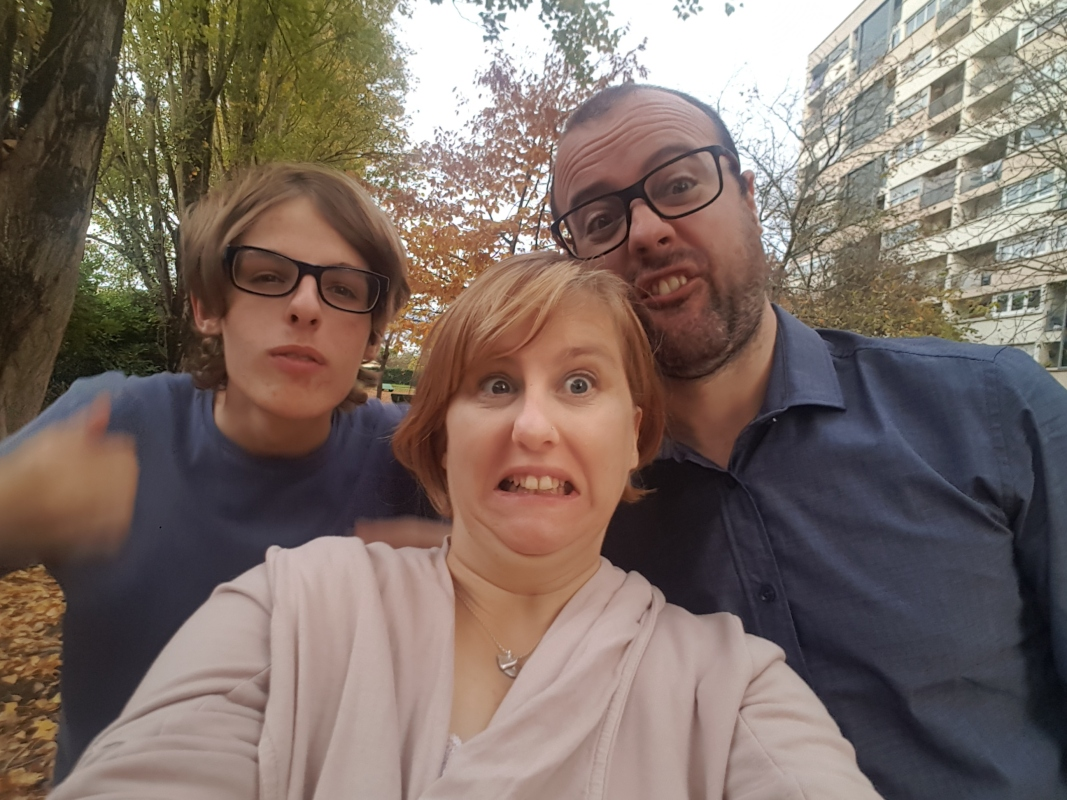 Picture of three people outside, taking a selfie and pulling funny faces. Behind them is a large, apartment building.