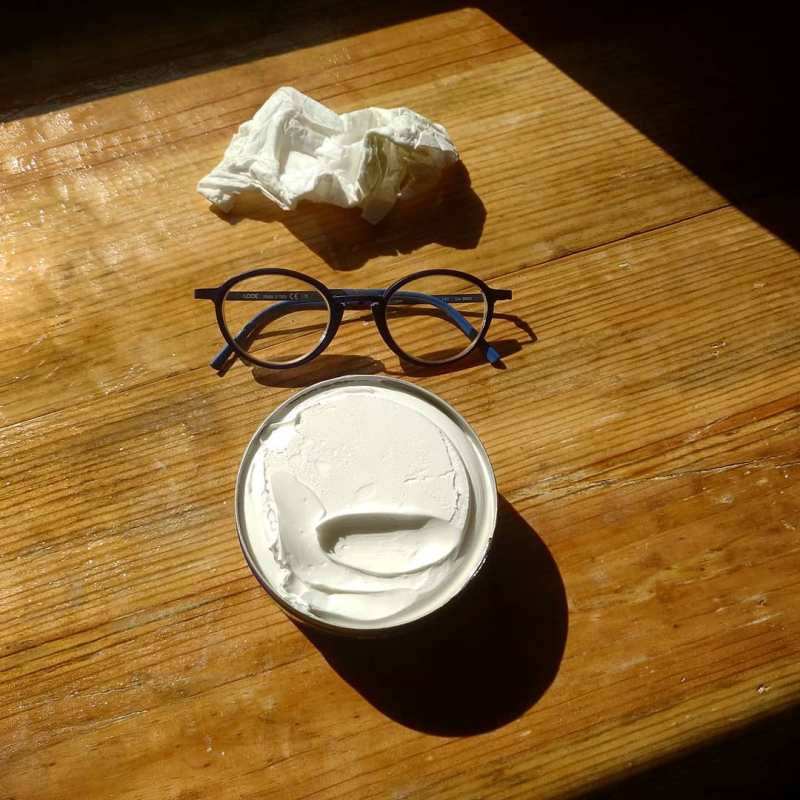 Photo of a crumped up tissue, a pair of glasses and a jar of white cream on a wooden table