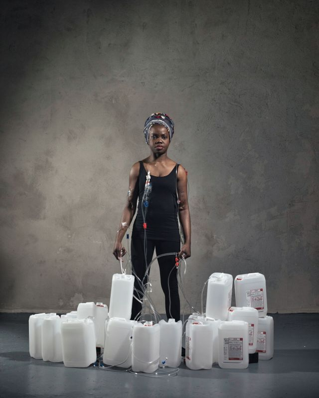 A person in a black sleeveless top and trousers, wearing a grey and red head wrap. They are looking forward at the camera, with dialysis tubing connected to her. They are standing behind a collection of empty plastic jugs.