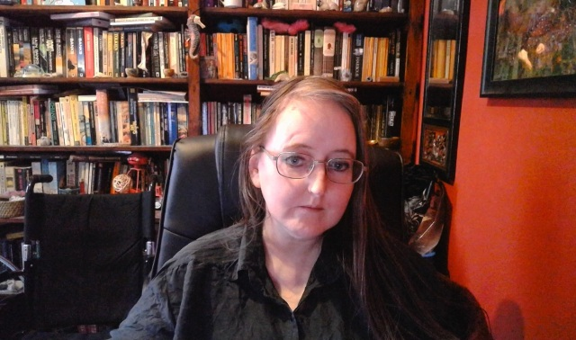 Image of a person with long, light-coloured hair sat on a black desk chair, wearing glasses and a black top. The person is sat next to an orange wall, with a framed picture and mirror. The background is a set of bookshelves full of books, and other items. A wheelchair with a black seat and handles is visible to the left of the image.