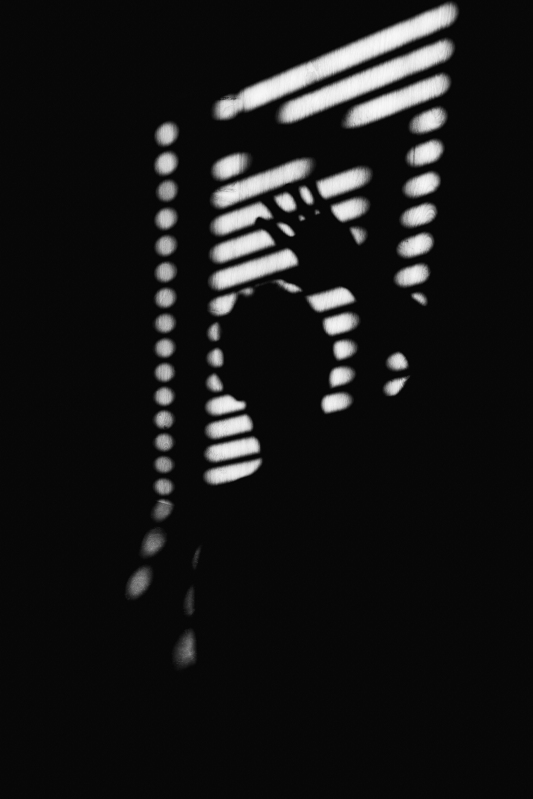Shadow of a figure in black and white with their hand reaching up, marked by venetian blinds.