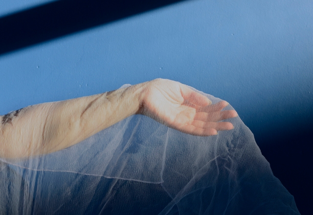 Image of a hand and arm, covered with white gauze material, against a blue background.