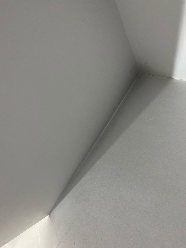 Photo of the corner of a ceiling, painted white, with a slight shadow.