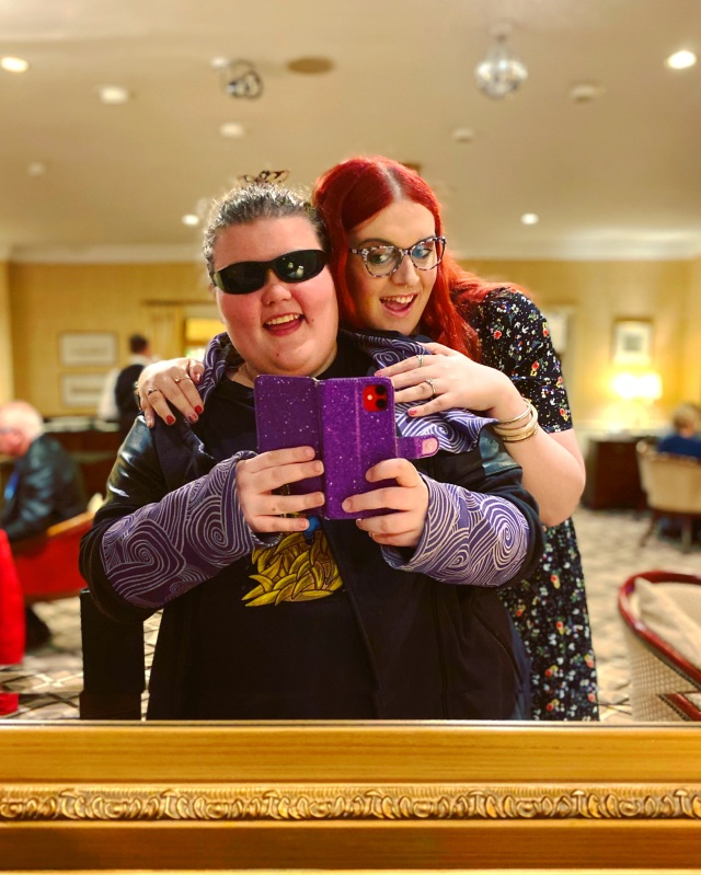 Image of two people taking a picture of their reflection in the mirror. Person holding the phone is wearing sunglasses, wearing a black and purple coat and is holding a purple phone case. They are being hugged by a person standing behind them with red hair and glasses, wearing a black and flowered dress. The background is a hotel lobby with yellow walls and beige and red chairs.