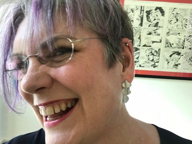 Photo of Pauline, who has purple hair, glasses and is smiling