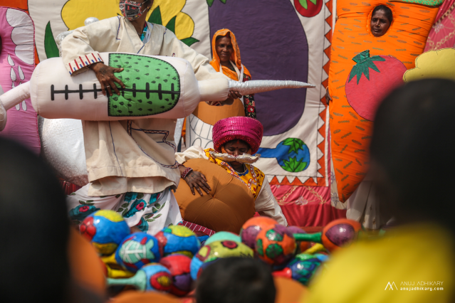 Colourful image of people dressed in costumes, holding a large needle. One person is fallen on the floor wearing a large belly costume.