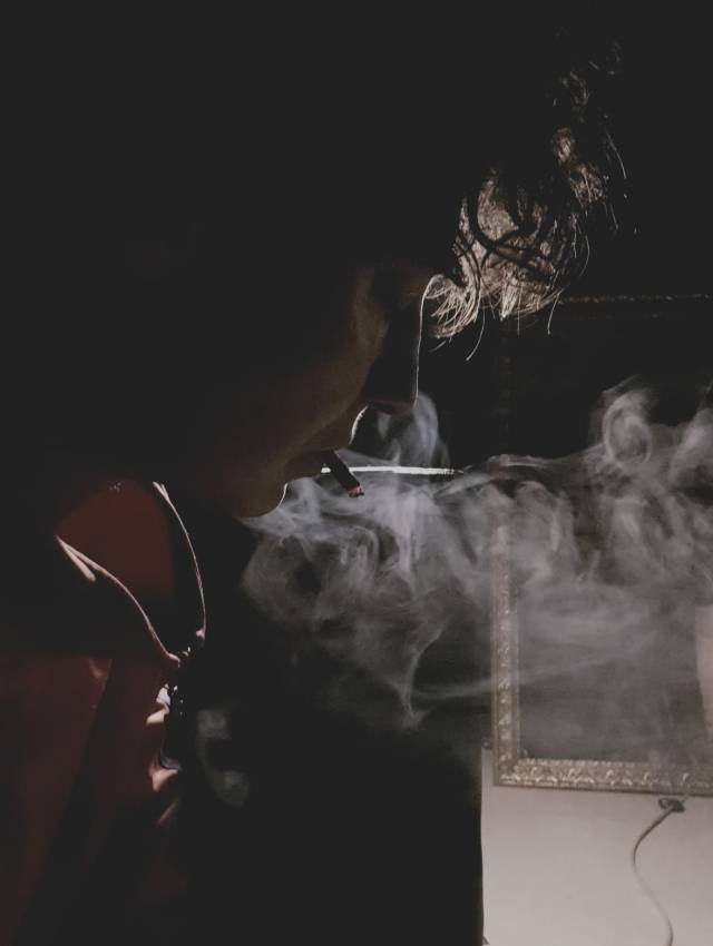Image of a person with curly hair with a cigarette in their mouth, surrounded by smoke. The lighting is from behind and lights up some of the hair and the edges of the persons cloth