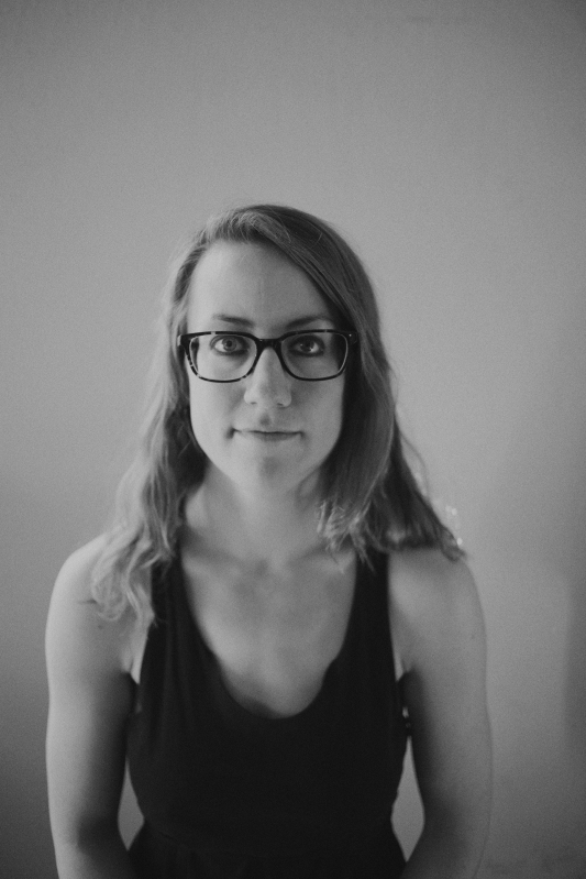 A black and white portrait of Ellen wearing a black dress and their glasses.